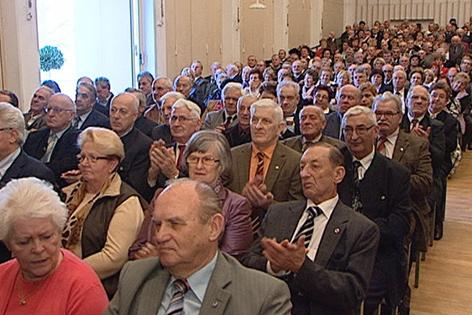 Senioren sitzen in einem Saal