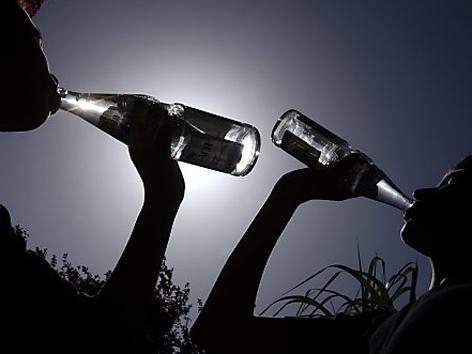 Zwei Personen trinken Wasser aus der Flasche.