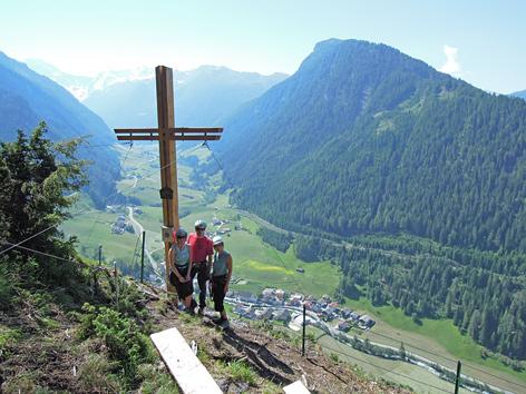 Bergsteiger bei einem Kreuz