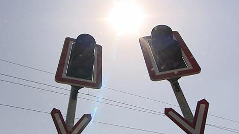 Ampel bei der Eisenbahn-Kreuzung mit Sonne im Hintergrund
