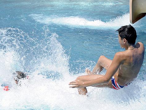 Kinder benutzen Wasserrutsche im Freibad