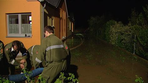 Feuerwehr in überschwemmten Garten beim Auspumpen