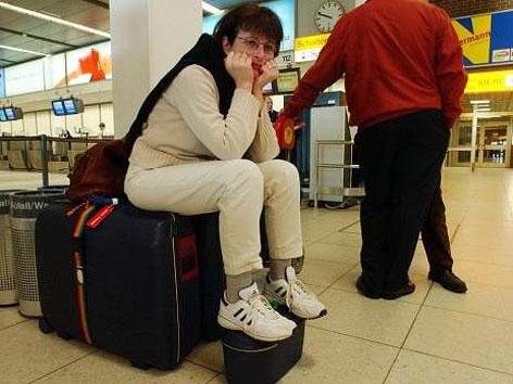 Flugreisende sitzt zermürbt auf ihrem Gepäck am Flughafen