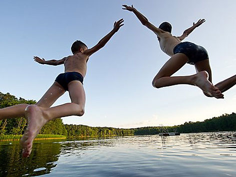 Zwei Jungen springen in einen See