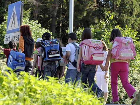 Lehrerin mit Volksschülern auf einem Schulweg