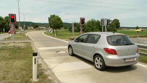 Auto hält vor roter Ampel bei Bahnübergang