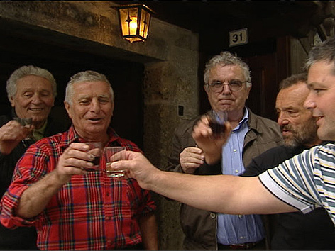 Männer beim Anstoßen mit Wein vor Osteria