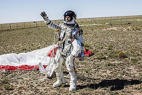 Baumgartner mit Raumanzug u Fallfschirm bei der Landung
