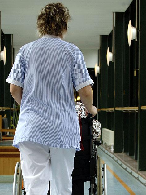 Pflegerin mit Patientin in Rollstuhl