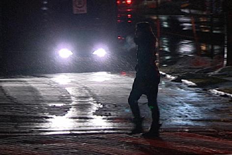 Dunkel gekleidete Fußgängerin überquert die Straße