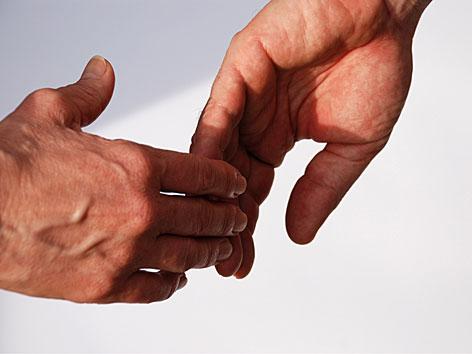 Zwei Hände, die einander loslassen