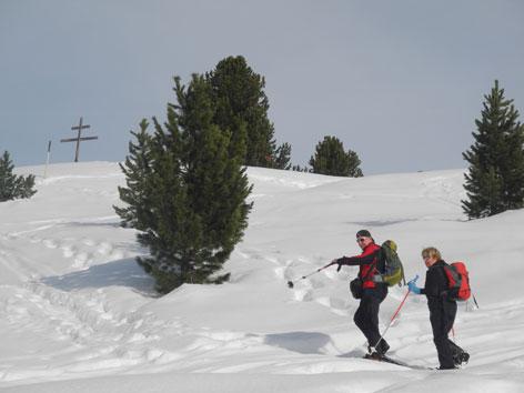 Zwei Tourengeher im Tiefschnee Richtung Gipfelkreuz