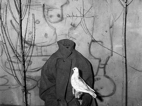 Fotografie von Roger Ballen: Eine Person ohne Kopf hält eine Taube