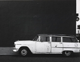 Foto von Lewis Baltz, dass ein weißes Auto vor einer kargen Wand zeigt