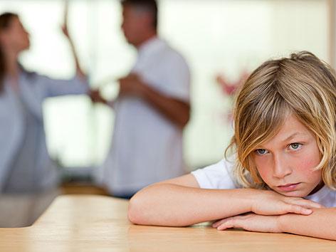 Ein Kind sieht traurig aus, im Hintergrund streiten sich die Eltern