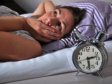 Eine Frau liegt im Bett und kann nicht schlafen. Der Wecker zeigt halb drei Uhr morgens