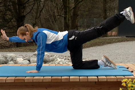 Doresia Krings führt eine Streckübung im Vierfüßlerstand vor, bei der Arm und Bein gegengleich gestreckt werden.
