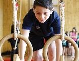 Junge turnt auf zwei Ringen