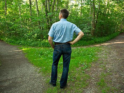 Ein Mann steht vor einer Weggabelung im Wald