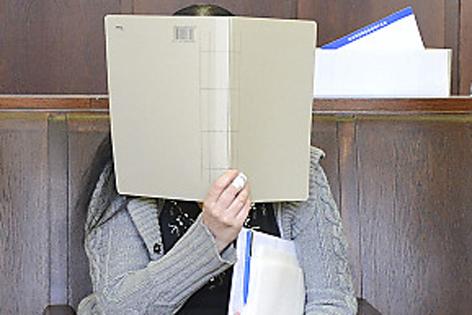 Angeklagte mit Mappe vor dem Gesicht