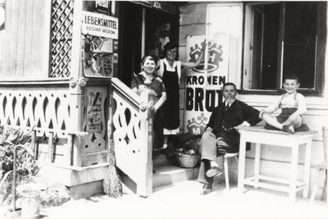 Schwarzweiß-Foto. Ein jüdisches Lebensmittelgeschäft, drei Erwachsene und ein Kind sitzen davor und lächeln in die Kamera.