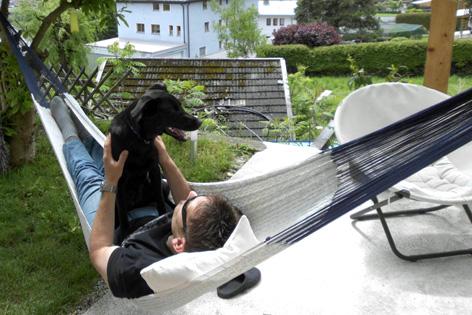 Hund und Herrl entspannen in der Hängematte