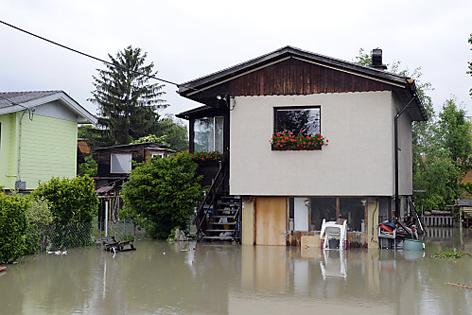 Haus steht auf Säulen, am Parkplatz schon das Hochwasser
