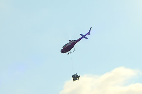 Hubschrauber in der Luft mit Abwurfbehälter