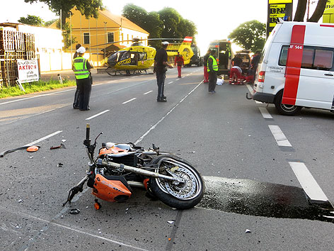 Einsatzkräfte der Rettung und Polizei am Mittwoch, 3. Juli 2013, bei Bergungsarbeiten an der Unfallstelle nachdem ein Biker mit einem Pkw auf der Brünner Straße in Floridsdorf kollidierte.