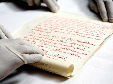 """Ein Schriftstück, gezeichnet von """"Alfons Riedel, Bildhauer"""" das in einem Behältnis unter der Steinfigur des gefallenen Soldaten in der Krypta im Wiener Burgtor gefunden wurde"""