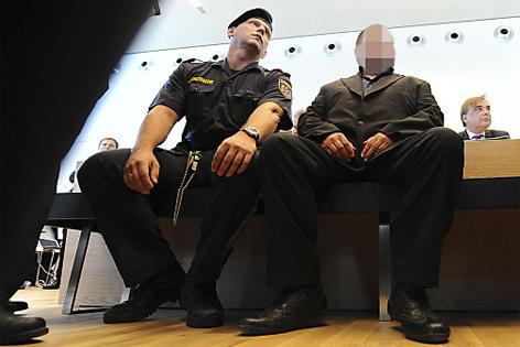 Angeklagter mit Polizisten im Gerichtssaal