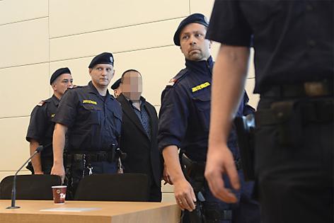 Angeklagter wird vom Polizisten begleitet