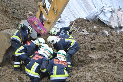 Bagger und Feuerwehrleute bei Bergungsarbeiten nach Hangrutsch