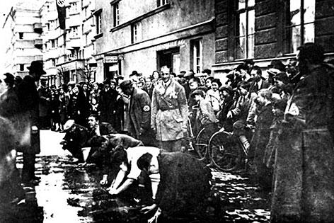 Juden, die im März 1938 in der Hagenmüllergasse gezwungen wurden, die Straße von politischen Parolen zu säubern.