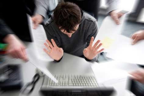 Mann sitzt am Computer und hat Stress