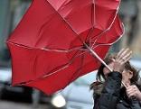 Passantin mit Regenschirm bei Wind
