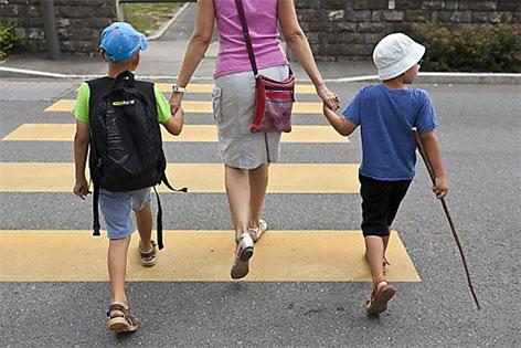 Frau geht mit zwei Kindern über Zebrastreifen