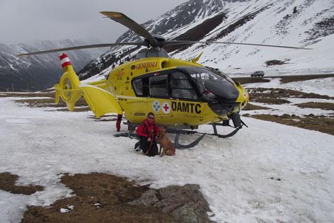 Lawinenhund und Hundeführer vor ÖAMTC Hubschrauber