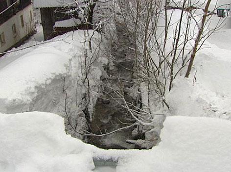 Bach inmitten eines tief verschneiten Ortsgebiets