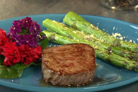 Spargel und Steak am Teller mit Blütendekoration