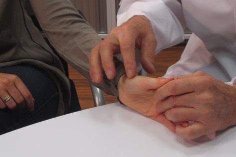 Arzt befühlt das Fingergelenk eines Patienten