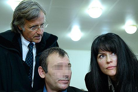 Die Anwälte Elmar Kresbach (L.), Liane Hirschbrich und der Anklagte vor Beginn eines Prozesses nach einen Mord im Skaterpark in Meidling