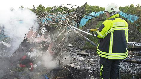 Feuerwehr löscht ausgebranntes Flugzeugwrack