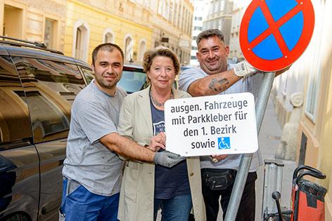 Stenzel und zwei Bauarbeiter mit dem neuen Verkehrsschild plus Hinweistafel