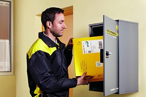 Zusteller gibt Paket in Box