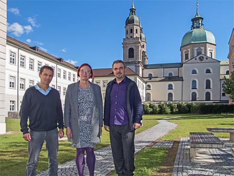 Drei Menschen im Garten vor Universität und Kirche
