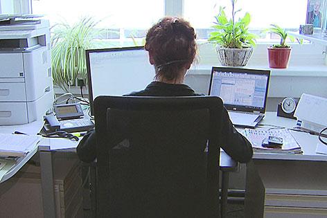 Frau sitzt im Büro am Schreibtisch vor dem Computer