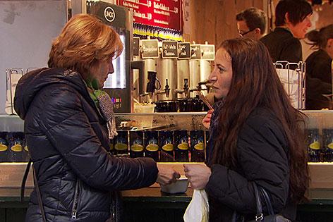 Frauen stehen am Glühweinstand am Salzburger Christkindlmarkt