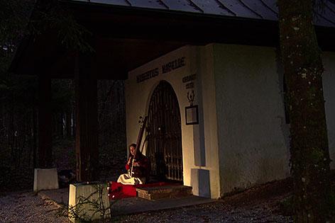 Sitarspielerin vor abendlicher Kapelle