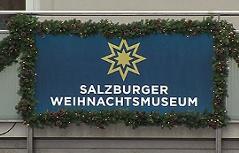 Schild mit Logo des Weihnachtsmuseums am Mozartplatz in der Stadt Salzburg